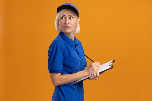 Onder de indruk blonde bezorger van middelbare leeftijd in blauw uniform en pet