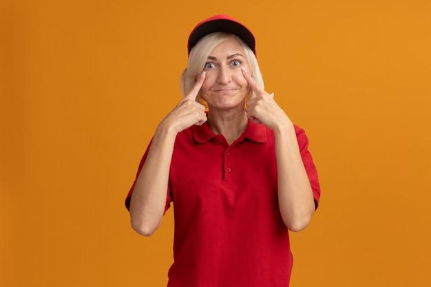Onder de indruk blonde bezorger van middelbare leeftijd in rood uniform en pet die oogleden naar beneden trekt en lippen tuit