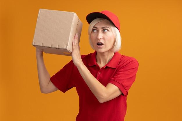 Onder de indruk blonde bezorger van middelbare leeftijd in rood uniform en pet houden en kijken naar kartonnen doos geïsoleerd op oranje muur met kopieerruimte