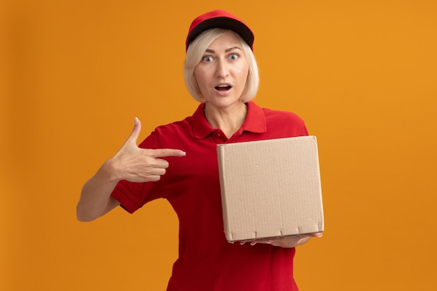 Onder de indruk blonde bezorger van middelbare leeftijd in rood uniform en pet houden en wijzend op kartonnen doos kijkend naar voorkant geïsoleerd op oranje muur met kopieerruimte
