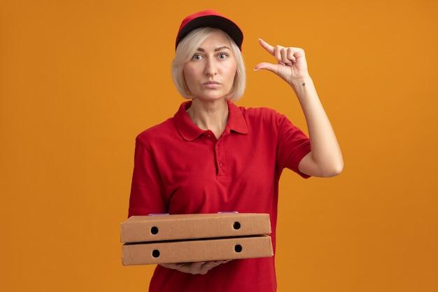Onder de indruk blonde bezorger van middelbare leeftijd in rood uniform en pet met pizzapakketten die naar de voorkant kijken en een klein bedrag gebaar doen geïsoleerd op een oranje muur met kopieerruimte