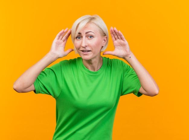 Onder de indruk blonde slavische vrouw van middelbare leeftijd die camera bekijkt die handen dichtbij hoofd houdt dat op gele achtergrond wordt geïsoleerd
