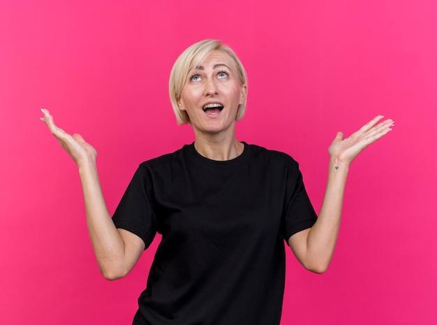 Onder de indruk blonde slavische vrouw van middelbare leeftijd die omhoog het tonen van lege die handen op roze muur toont kijken