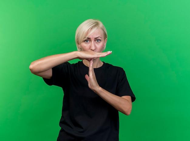 Onder de indruk blonde slavische vrouw van middelbare leeftijd die time-outgebaar doet dat op groene muur met exemplaarruimte wordt geïsoleerd