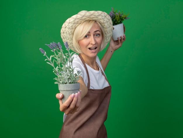 Onder de indruk blonde tuinmanvrouw in uniform met hoed die in profielweergave staat met bloempot en een andere naar voren uitstrekt en naar voren kijkt