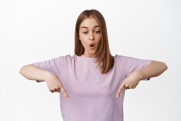 Onder de indruk blonde vrouw die naar beneden wijst, naar de advertentie hieronder kijkt met een hijgend verbaasd gezicht, in een t-shirt over een witte muur