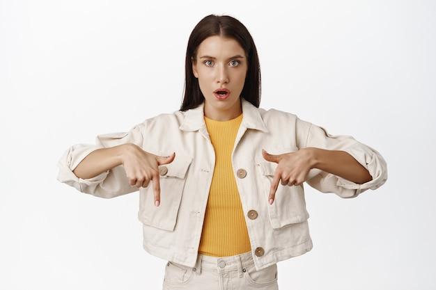 Onder de indruk brunette vrouw praat over reclame, wijzende vingers naar beneden op kopieerruimte met kortingslogo voor de verkoop, banner tonen, open mond gefascineerd op wit.