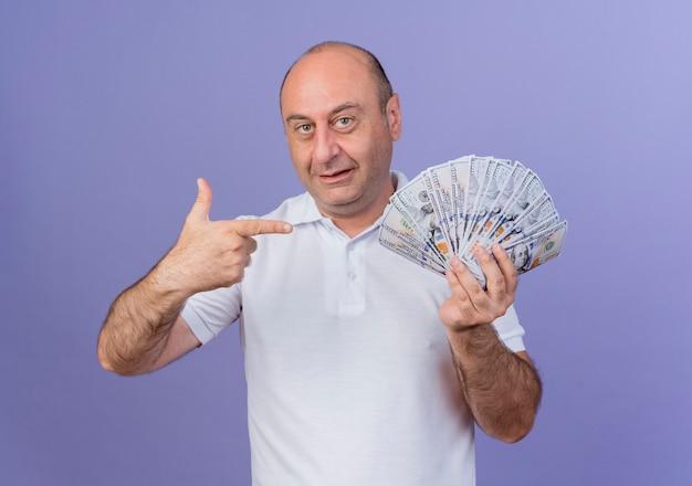 Onder de indruk casual volwassen zakenman bedrijf en wijzend op geld geïsoleerd op paars