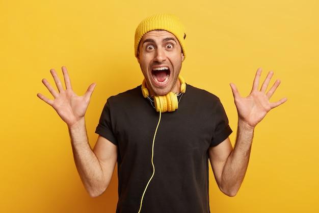 Onder de indruk dolgelukkig jongeman schreeuwt emotioneel, toont beide handpalmen, draagt gele hoed
