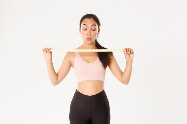 Onder de indruk en gelukkig aziatische vrouwelijke atleet weergegeven: meetlint na maatregel taille en afvallen met trainingsprogramma, gaan in de sportschool.