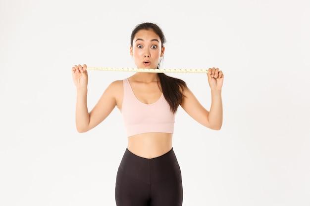Onder de indruk en gelukkig aziatische vrouwelijke atleet weergegeven: meetlint na taille mease en afvallen met trainingsprogramma, gaan in de sportschool.
