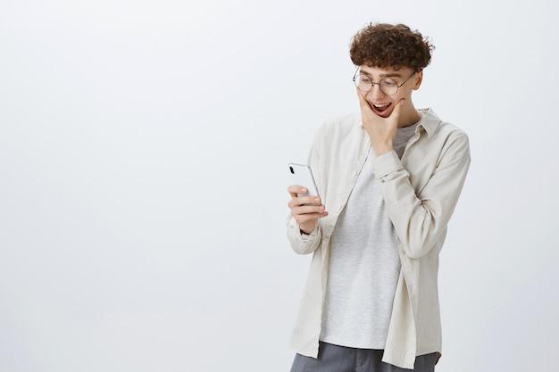 Onder de indruk en geschokte tiener die tegen de witte muur poseert