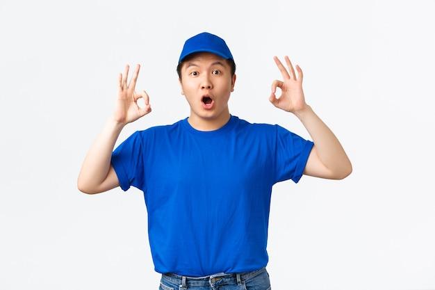 Onder de indruk en verbaasde aziatische koerier in blauw uniform reageren op super coole promo-aanbieding. bezorger in pet en t-shirt met goed gebaar, prijs goed werk, goed gedaan, complimenteer geweldige keuze