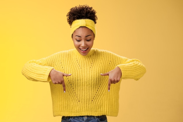 Onder de indruk enthousiast lachende gefascineerde afro-amerikaanse vrouw in trui hoofdband kijken wijzend doen...