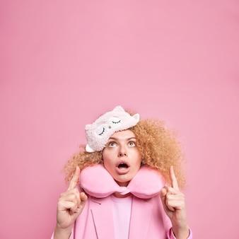 Onder de indruk gekrulde jonge vrouw houdt mond open, wijst op mededelingen boven het hoofd