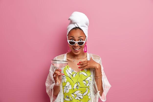 Onder de indruk gelukkig donkerhuidig etnisch vrouwelijk model houdt alcoholische cocktail, draagt een stijlvolle zonnebril, gewikkeld badhanddoek op het hoofd, besteedt vrije tijd op pyjamafeestje, poseert tegen roze muur