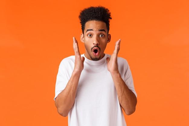 Onder de indruk, geschrokken afro-amerikaanse man die iets geweldigs ziet, hijgend vroeg zich af en geamuseerd, check-out kortingen, seizoensverkoop, woon verbluffende prestaties bij, staande oranje achtergrond.
