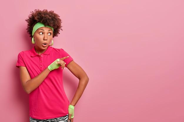 Onder de indruk geschrokken vrouw met donkere huid kijkt met verwondering, paniek en wijst weg, sprakeloos achtergelaten over de schokkende gebeurtenis die is gebeurd, draagt groene hoofdband, t-shirt en sporthandschoenen