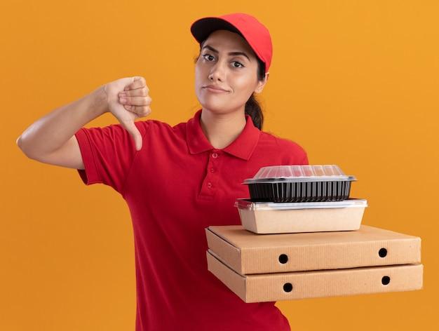 Onder de indruk jong bezorgmeisje die uniform en pet dragen die pizzadozen met voedselcontainers houden die duim neer tonen geïsoleerd op oranje muur