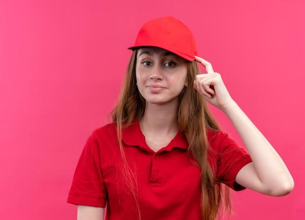 Onder de indruk jong bezorgmeisje in rood uniform vinger op hoofd zetten geïsoleerde roze ruimte met kopie ruimte