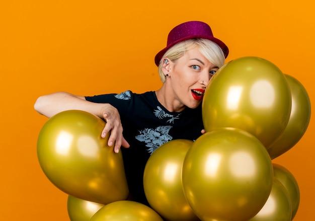 Onder de indruk jong blond feestmeisje met feestmuts achter ballonnen aanraken en kijken naar camera geïsoleerd op een oranje achtergrond