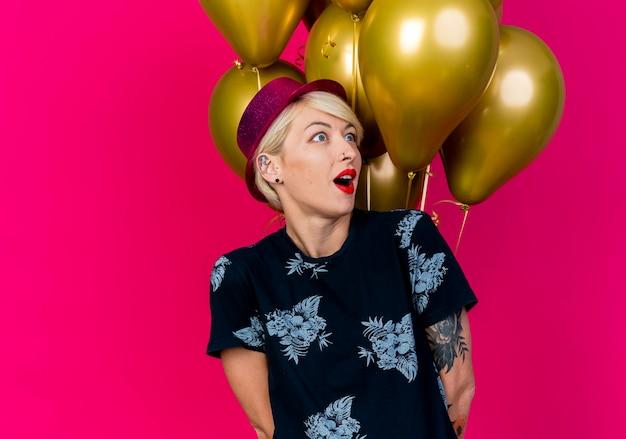 Onder de indruk jong blond feestmeisje met feestmuts staan voor ballonnen kijken kant houden handen achter rug geïsoleerd op karmozijnrode achtergrond met kopie ruimte