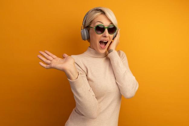 Onder de indruk jong blond meisje met een zonnebril en een koptelefoon die de hand op een koptelefoon zet met lege hand geïsoleerd op een oranje muur met kopieerruimte