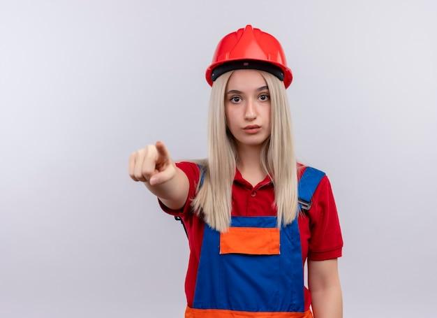 Onder de indruk jong blond meisje van de ingenieursbouwer in uniform richtend op geïsoleerde witte ruimte met exemplaarruimte