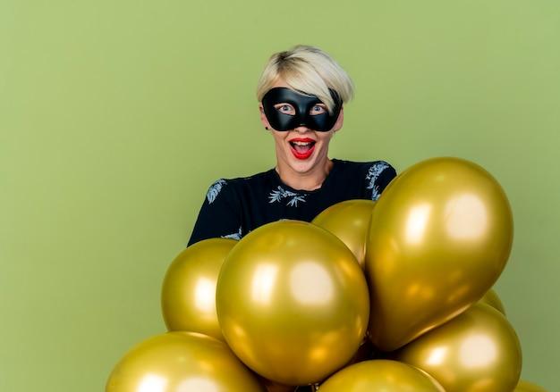 Onder de indruk jong blond partijmeisje die maskerademasker dragen die zich achter ballons bevinden die camera bekijken die op olijfgroene achtergrond met exemplaarruimte wordt geïsoleerd