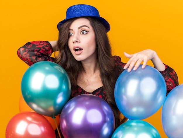 Onder de indruk jong feestmeisje met een feesthoed die achter ballonnen staat en een hand achter het hoofd aanraakt en naar de zijkant kijkt die op een oranje muur is geïsoleerd