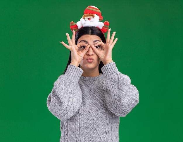 Onder de indruk jong kaukasisch meisje dat de hoofdband van de kerstman draagt die camera bekijkt die blikgebaar doet die handen als verrekijker gebruikt die op groene achtergrond wordt geïsoleerd