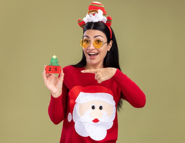 Onder de indruk jong kaukasisch meisje dragen hoofdband van de kerstman en trui met bril houden kerstboom speelgoed met datum wijzend naar camera kijken geïsoleerd op olijfgroene achtergrond