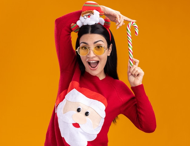 Onder de indruk jong kaukasisch meisje dragen hoofdband van de kerstman en trui met bril met traditionele kerst candy cane in de buurt van hoofd kijken naar camera geïsoleerd op een oranje achtergrond