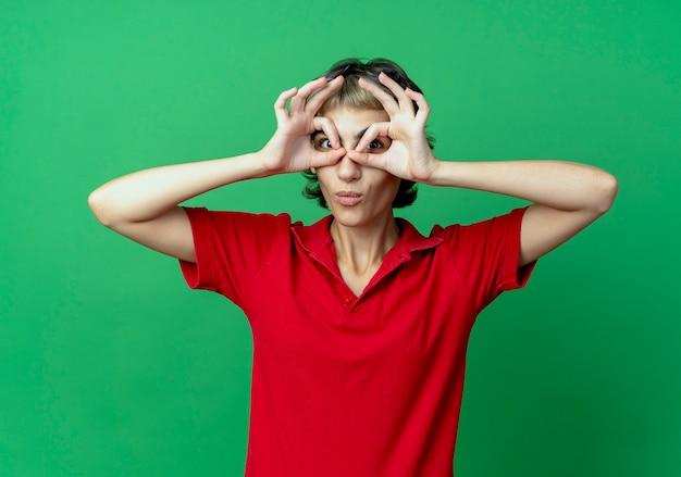 Onder de indruk jong kaukasisch meisje met pixiekapsel die blikgebaar doen die handen als verrekijker gebruiken die op groene achtergrond worden geïsoleerd