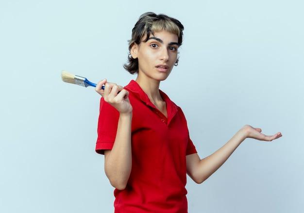 Onder de indruk jong kaukasisch meisje met pixiekapsel die de kwast houden die lege die hand toont op witte achtergrond wordt geïsoleerd