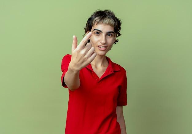 Onder de indruk jong kaukasisch meisje met pixiekapsel die kom hier gebaar bij camera doen die op olijfgroene achtergrond met exemplaarruimte wordt geïsoleerd