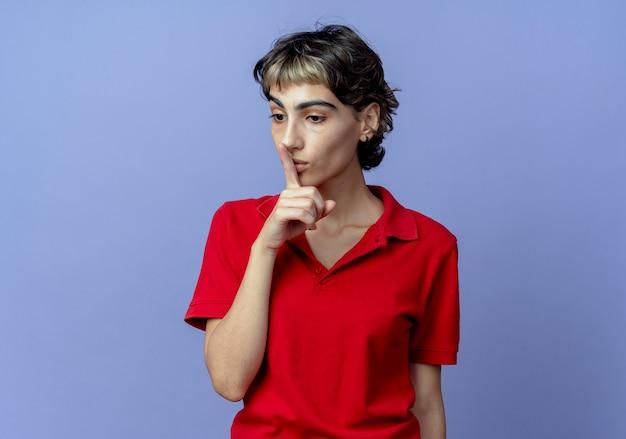 Onder de indruk jong kaukasisch meisje met pixiekapsel die naar beneden en gebaren stilte kijken die op purpere achtergrond met exemplaarruimte wordt geïsoleerd