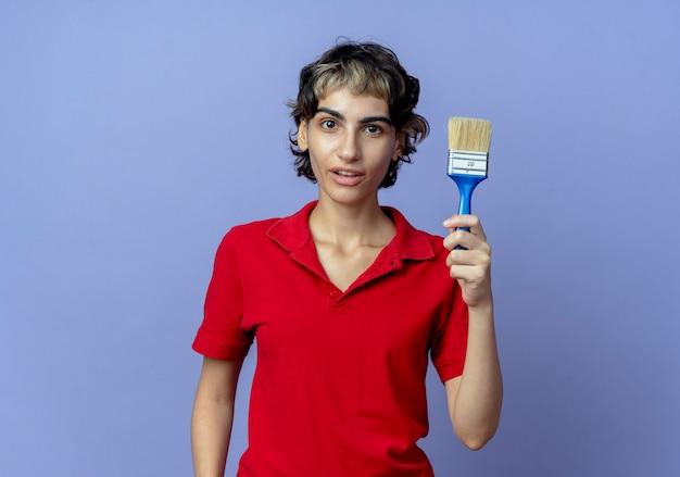 Onder de indruk jong kaukasisch meisje met pixiekapsel die verfborstel houden die op purpere achtergrond met exemplaarruimte wordt geïsoleerd
