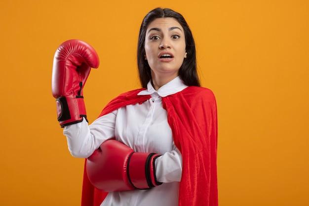 Onder de indruk jong kaukasisch superheromeisje die dooshandschoenen dragen die hand in lucht houden die camera bekijken die op oranje achtergrond met exemplaarruimte wordt geïsoleerd