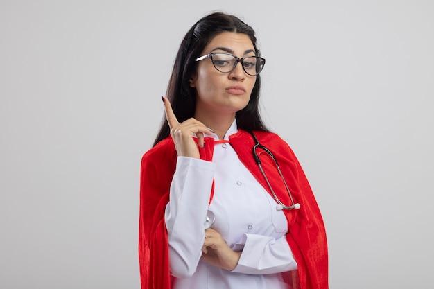 Onder de indruk jong kaukasisch superheromeisje die glazen en stethoscoop dragen die omlaag wijzen die omhoog wijzen geïsoleerd op witte achtergrond met exemplaarruimte