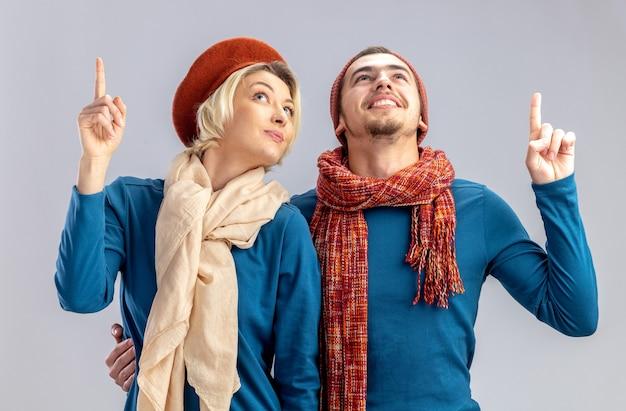 Onder de indruk jong koppel opzoeken op valentijnsdag met hoed met sjaal wijst naar omhoog geïsoleerd op witte achtergrond on