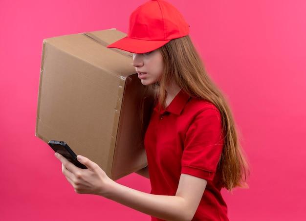 Onder de indruk jong leveringsmeisje in rode uniforme holdingsdoos en mobiele telefoon die mobiele telefoon bekijken die zich in profielmening bevinden op geïsoleerde roze ruimte