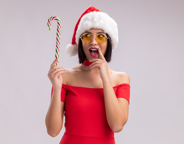 Onder de indruk jong meisje dragen kerstmuts en bril houden en kijken naar kerst candy cane aanraken lip geïsoleerd op een witte achtergrond met kopie ruimte
