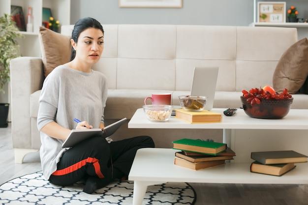 Onder de indruk jong meisje gebruikte laptop schrijft op notebook zittend op de vloer achter de salontafel in de woonkamer