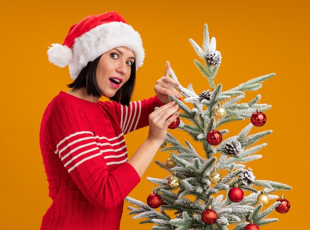 Onder de indruk jong meisje met kerstmuts staande in profiel te bekijken in de buurt van de kerstboom versieren het met kerstballen kijken camera geïsoleerd op een oranje achtergrond