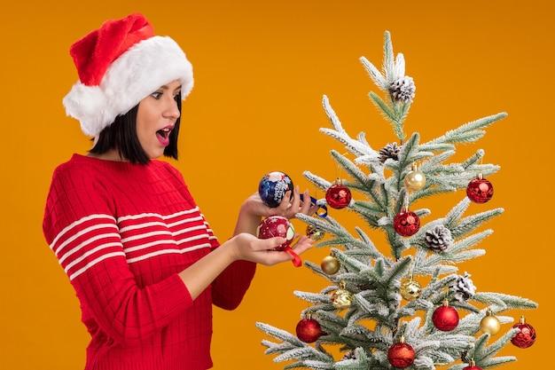 Onder de indruk jong meisje met kerstmuts staande in profiel te bekijken in de buurt van versierde kerstboom houden en kijken naar kerstballen geïsoleerd op oranje muur