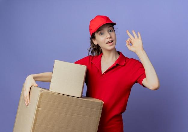 Onder de indruk jong mooi bezorgmeisje dat een rood uniform draagt en een pet met kartonnen dozen en ok teken doet dat op paarse achtergrond wordt geïsoleerd