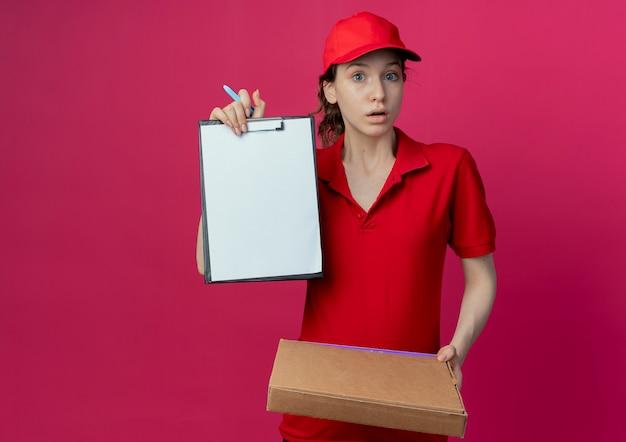 Onder de indruk jong mooi bezorgmeisje in rood uniform en pet die pizzapakketpen houdt en klembord toont dat op karmozijnrode achtergrond met exemplaarruimte wordt geïsoleerd