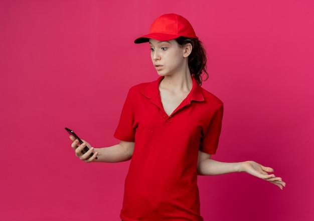 Onder de indruk jong mooi bezorgmeisje in rood uniform en pet houden en kijken naar mobiele telefoon en tonen lege hand geïsoleerd op een karmozijnrode achtergrond