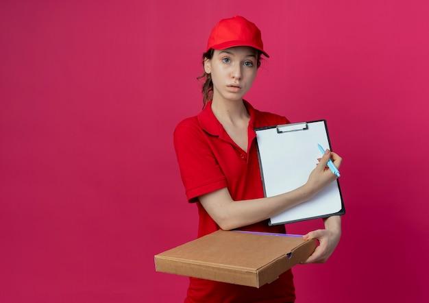 Onder de indruk jong mooi bezorgmeisje in rood uniform en pet met pizzapakket en klembord wijzend met pen op klembord geïsoleerd op karmozijnrode achtergrond met kopie ruimte